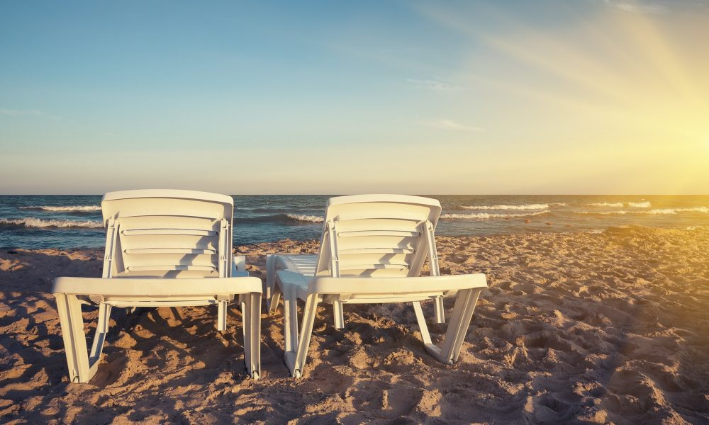 Two deckchairs on the beach with bright sun and waves